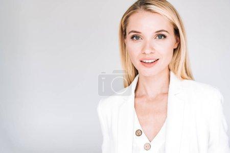 lächelnd schöne junge blonde Frau in insgesamt weißen Outfit isoliert auf grau