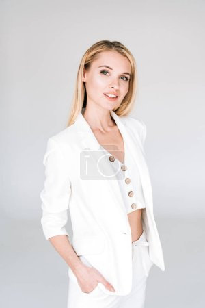 beautiful young blonde woman in total white outfit with hands in pockets isolated on grey