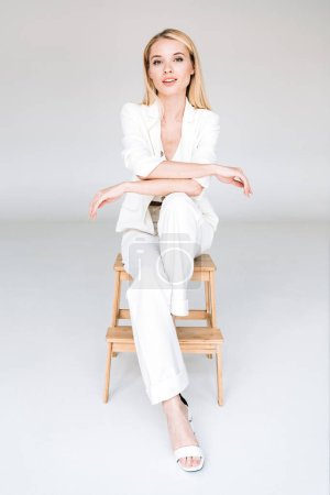 smiling beautiful young blonde woman in total white outfit sitting on chair