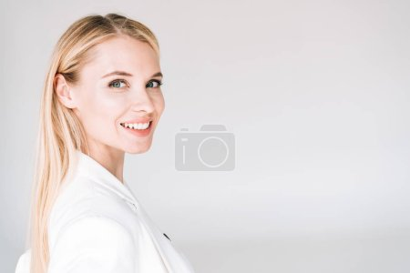 Photo for Smiling beautiful young blonde woman isolated on grey - Royalty Free Image