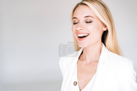 Photo for Happy beautiful young blonde woman in total white outfit with closed eyes isolated on grey - Royalty Free Image