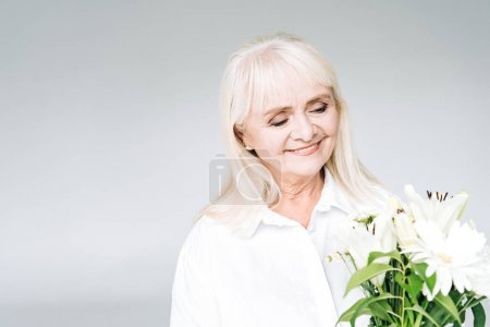 happy blonde senior woman in white clothes with flowers isolated on grey