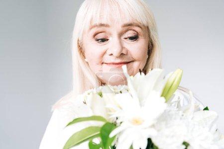 Photo pour Femme aînée blonde de sourire dans des vêtements blancs regardant des fleurs d'isolement sur le gris - image libre de droit
