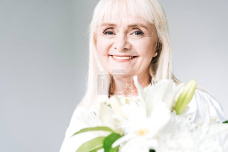 Photo for Happy blonde senior woman in white clothes holding flowers isolated on grey - Royalty Free Image