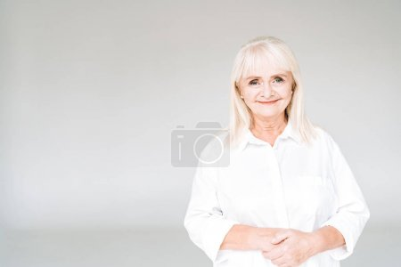 Photo for Happy blonde senior woman in white clothes isolated on grey - Royalty Free Image