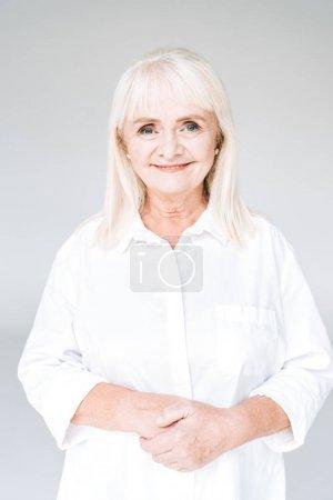 Photo pour Femme aînée blonde heureuse dans des vêtements blancs regardant l'appareil-photo isolé sur le gris - image libre de droit