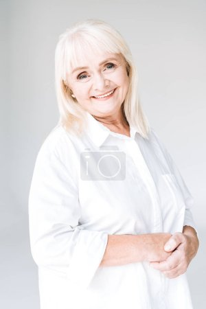Photo for Happy blonde senior woman in white outfit isolated on grey - Royalty Free Image