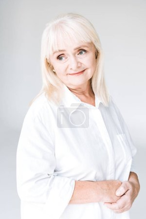 Photo for Dreamy blonde senior woman in white clothes looking away isolated on grey - Royalty Free Image