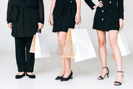 Photo for Cropped view of fashionable three-generation women in total black outfits with shopping bags isolated on grey - Royalty Free Image