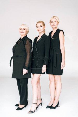 Photo pour Vue pleine longueur de la mode trois générations femmes blondes dans des tenues noires totales isolés sur le gris - image libre de droit