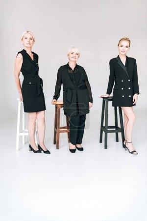 Photo pour Vue pleine longueur des femmes blondes à la mode de trois générations dans des tenues noires totales près de chaises isolées sur gris - image libre de droit