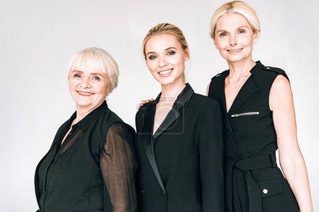 Foto de Feliz de moda mujeres rubias de tres generaciones en trajes negros totales aislados en gris - Imagen libre de derechos