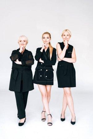 Photo pour Vue pleine longueur des femmes blondes à la mode de trois générations dans les tenues noires totales posant d'isolement sur le gris - image libre de droit