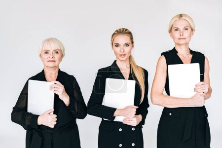 Photo pour À la mode trois générations femmes d'affaires blondes dans des tenues noires totales avec des planches blanches isolées sur le gris - image libre de droit