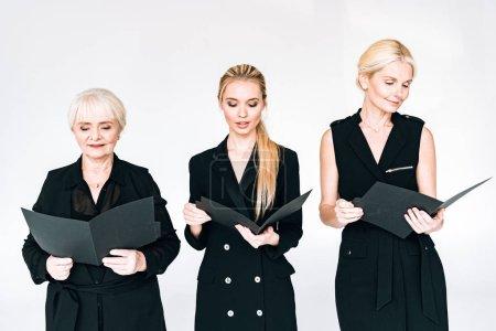 Photo pour À la mode trois générations femmes d'affaires blondes dans des tenues noires totales avec des dossiers isolés sur le gris - image libre de droit