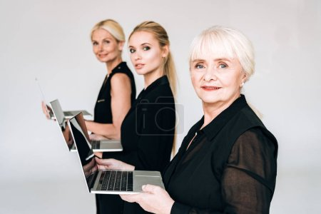 Photo for Side view of fashionable three-generation blonde businesswomen in total black outfits holding laptops isolated on grey - Royalty Free Image