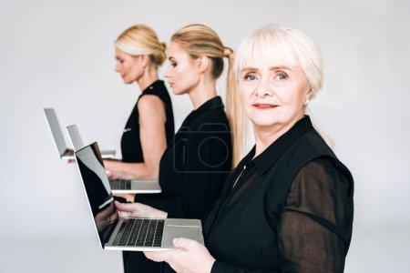 Photo pour Vue latérale de femmes d'affaires blondes de trois générations en tenue noire totale tenant des ordinateurs portables isolés sur gris - image libre de droit