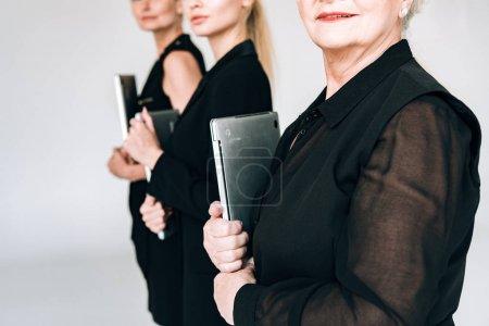 Foto de Vista recortada de mujeres de negocios rubias de tres generaciones en trajes negros totales que sostienen portátiles aislados en gris - Imagen libre de derechos