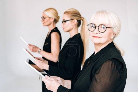 Photo pour À la mode trois générations femmes d'affaires blondes dans des tenues noires totales et des lunettes tenant des tablettes numériques isolées sur le gris - image libre de droit