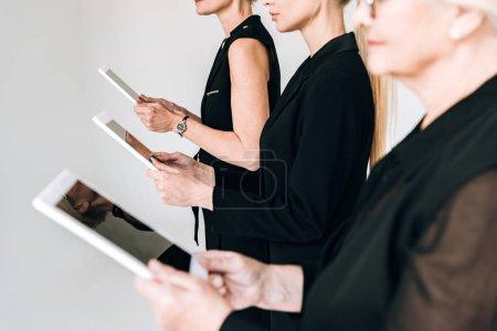 Photo pour Vue partielle des femmes d'affaires blondes à la mode de trois générations dans les tenues et les lunettes noires totales retenant des comprimés numériques d'isolement sur le gris - image libre de droit