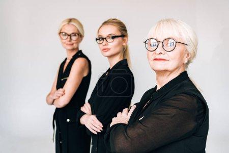 Photo pour Focus sélectif des femmes d'affaires blondes à la mode de trois générations dans des tenues noires totales et des lunettes isolées sur le gris - image libre de droit