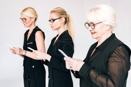 Photo pour À la mode trois générations femmes d'affaires blondes dans des tenues noires totales et des lunettes en utilisant des smartphones isolés sur le gris - image libre de droit