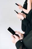 """Постер, картина, фотообои """"обрезанный вид бизнес-леди в общей черной одежды с помощью смартфонов изолированы на серый"""""""