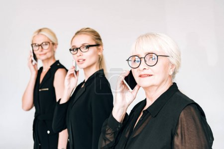 fashionable three-generation blonde businesswomen in total black outfits and glasses talking on smartphones isolated on grey