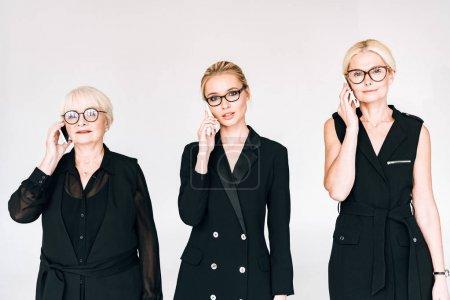 Photo pour Femmes d'affaires à la mode de trois générations dans des tenues noires totales et des lunettes parlant sur des smartphones isolés sur le gris - image libre de droit
