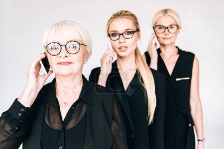 Photo pour Femmes d'affaires à la mode de trois générations parlant sur les smartphones isolés sur le gris - image libre de droit
