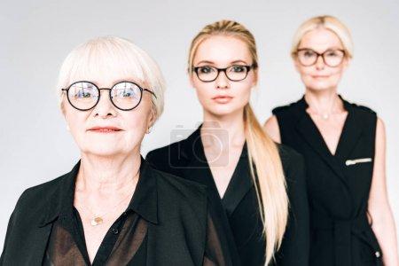 Foto de Mujeres de negocios rubias de tres generaciones de moda en gafas aisladas en gris - Imagen libre de derechos