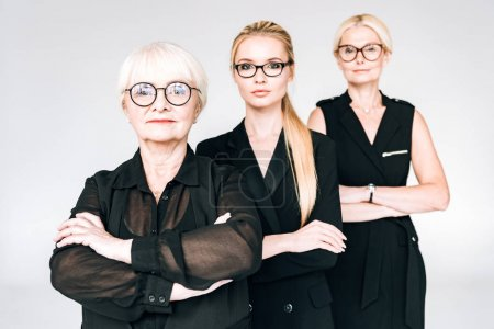 Foto de Mujeres de negocios rubias de tres generaciones de moda en gafas con los brazos cruzados aislados en gris - Imagen libre de derechos