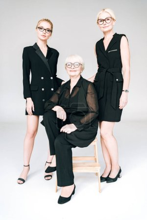Photo pour Vue pleine longueur des femmes d'affaires blondes à la mode de trois générations dans des lunettes avec les bras croisés isolés sur gris - image libre de droit