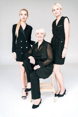 full length view of elegant three-generation blonde women in total black outfits isolated on grey