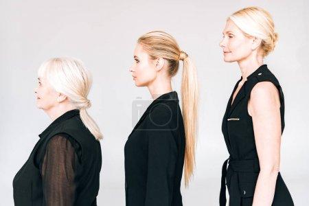 Photo pour Vue latérale d'élégantes femmes blondes de trois générations dans des tenues noires totales isolées sur le gris - image libre de droit