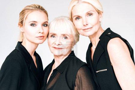 Photo pour Portrait d'élégantes femmes blondes de trois générations dans des tenues noires totales isolées sur le gris - image libre de droit