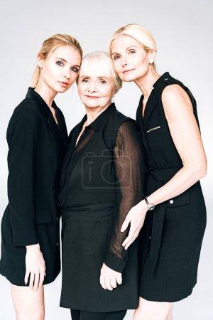 Photo pour Élégantes femmes de trois générations dans des tenues noires totales isolées sur le gris - image libre de droit