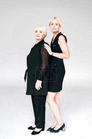 Photo pour Vue pleine longueur de fille mature blonde élégante et mère aînée dans des tenues noires totales isolées sur gris - image libre de droit