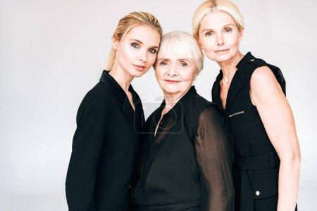 Foto de Elegante mujeres rubias de tres generaciones en trajes negros totales aislados en gris - Imagen libre de derechos