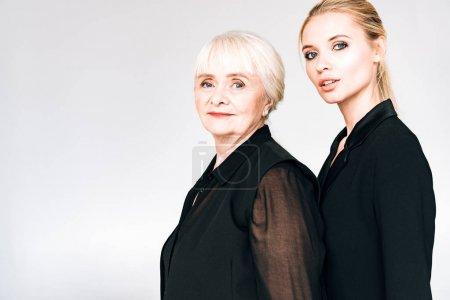 Photo pour Élégante petite-fille blonde et grand-mère dans des tenues noires totales isolées sur le gris - image libre de droit
