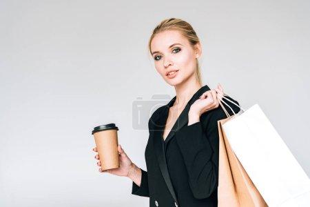 Photo pour Élégante femme blonde en tenue noire avec sacs à provisions et café pour aller isolé sur gris - image libre de droit
