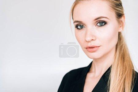 Photo pour Verticale de femme blonde élégante dans la tenue noire d'isolement sur le gris - image libre de droit