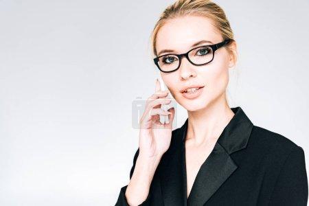 Photo pour Femme d'affaires blonde élégante dans la tenue noire et les glaces parlant sur le smartphone d'isolement sur le gris - image libre de droit