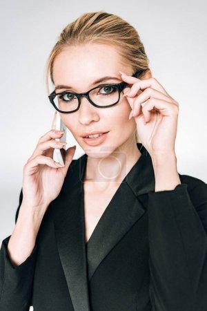 Photo pour Femme d'affaires blonde en tenue noire et lunettes parlant sur smartphone isolé sur gris - image libre de droit