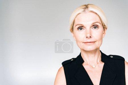 Photo pour Femme mûre élégante de sourire dans la tenue noire d'isolement sur le gris - image libre de droit