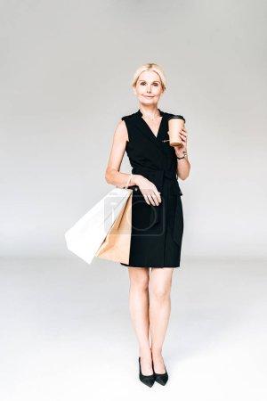Photo pour Vue pleine longueur de l'élégante femme blonde en tenue noire avec des sacs à provisions et du café pour aller isolé sur gris - image libre de droit