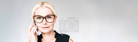 Photo for Panoramic shot of mature businesswoman in black outfit and glasses talking on smartphone isolated on grey - Royalty Free Image