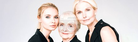 Photo for Panoramic shot of three-generation blonde women in total black outfits isolated on grey - Royalty Free Image
