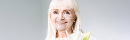 Photo pour Tir panoramique de la femme aînée blonde heureuse dans les vêtements blancs retenant des fleurs d'isolement sur le gris - image libre de droit