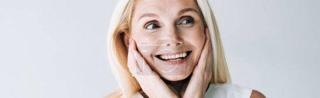 Panoramaaufnahme einer glücklichen blonden reifen Frau mit Händen in der Nähe des Gesichts, die isoliert von grau wegschaut